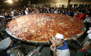 Big Food: Pizza makers surround a giant pizza