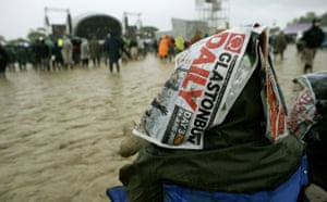 Glastonbury at 40:  Revellers sit in the mud and rain