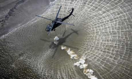 US national guard helicopters drop sandbags onto a breach near Grand Isle, Louisiana