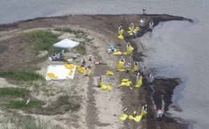 Deepwater Horizon: Gulf Oil Spill Begins To Reach Land :  Workers clean up oil along a beach