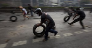 thailand clashes: Redshirts roll tyres to a burning barricade in Bangkok