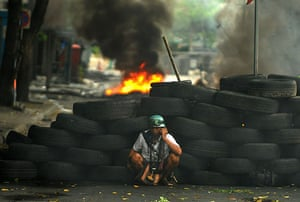 thailand clashes: A Redshirt protester shelters behind a barricade made of tyres in Bangkok