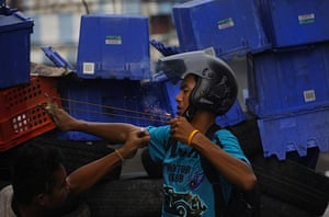 thailand clashes: An anti-government protester fires a firework on sling shot