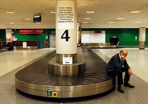Volcanic ash: Man sits on an empty luggage conveyor belt Edinburgh