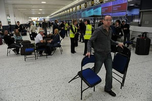 Volcanic ash: Staff hand out  chairs to passengers at Manchester Airport