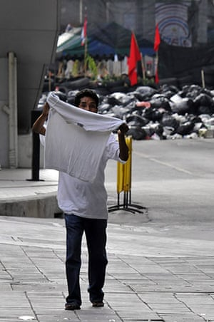 protests in Thailand: An anti government protester waves a white shirt as he surrenders