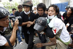 Bangkok protests: Anti government protesters evacuate an injured comrade during clashes