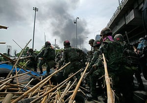 Bangkok protests: Soldiers charge through an anti-government barricade