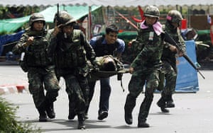 Bangkok protests: Soldiers carry a fellow soldier on a stretcher