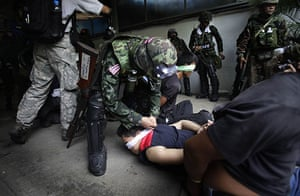 Bangkok crackdown: A soldier blindfolds an anti-government protester