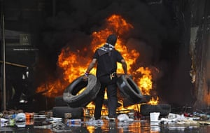 red shirt protesters: An anti-government protestor piles tires on a fire at a shopping centre