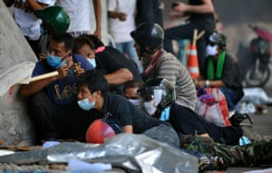 red shirt protesters: A group of hardline protesters take cover behind a wall