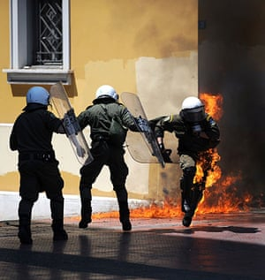 May Day protests: Athens, Greece: A riot policeman runs away from a fire