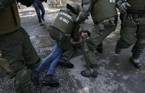 May Day protests: Santiago, Chile: A demonstrator is restrained by riot police