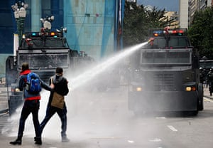 May Day protests: Bogota, Colombia: Riot police use a water cannon to disperse demonstrators
