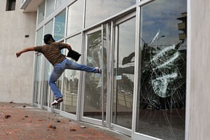 May Day protests: Cali, Colombia: A demonstrator smashes a glass door of the office of a bank