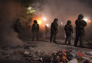 May Day protests: Berlin, Germany: Riot police stand next to burnt rubbish containers