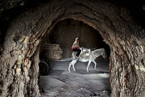 24 hours in pictures: Iraq: A girl rides a donkey at a brick factory