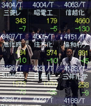 24 hours in pictures: Tokyo, Japan: Pedestrians are reflected in a stock index board