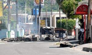 Jamaica: A resident stands by a road block in Kingston, Jamaica