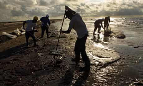 Workers hired by BP rake up oil in Louisiana