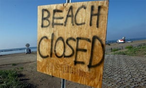 Oil spill, beach closed sign
