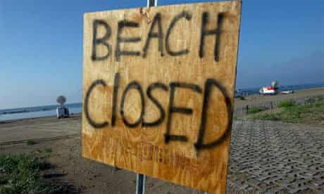 Oil spill, beach closed sign