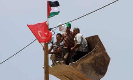 Workers hang Turkish and Palestinian flags at Gaza port