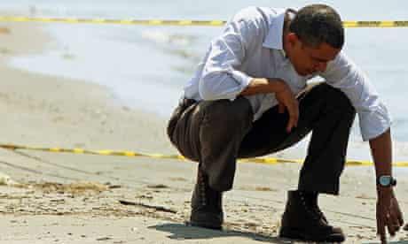 Barack Obama examines tar balls from the spill on a Louisiana beach last week. Photograph: EPA
