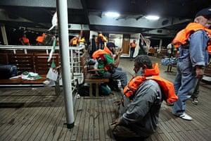 Gaza convoy attack: Activists wearing life jackets pray and wait on board the Mavi Marmara ship
