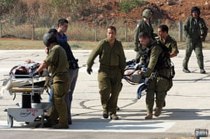 Gaza convoy attack: Israeli soldiers unload wounded people onto stretchers at Tel Aviv hospital