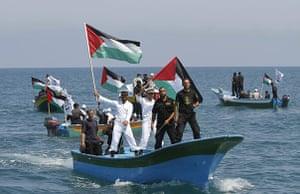 Gaza convoy attack: Hamas naval policemen, holding Palestinian flags, patrol the sea