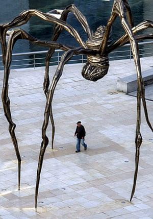 A man walks under Maman at the Guggenheim in Bilbao, Spain