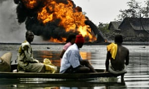 Niger Delta residents pass a burning Shell oil pipeline as they evacuate their homes by boat
