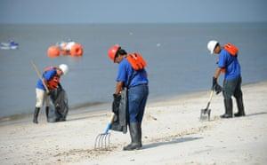 Deepwater Horizon oil rig: Oil spill : Men clean a beach in Biloxi, Mississippi