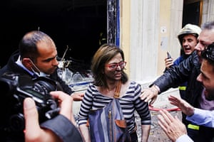 Greece Rioting: A bank employee is rescued from a fire in Athens