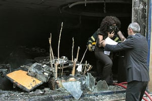 Greece Rioting: A woman is evacuated from the burning Marfin Bank building in Athens