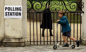 Voting Gallery: A school-boy passes a sign outside a polling station in London