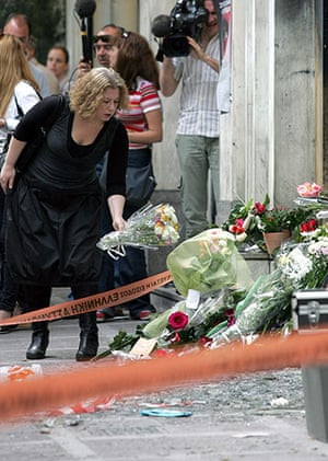 Greece Riots: A woman lays flowers outside the torched branch of Marfin Egnatia Bank