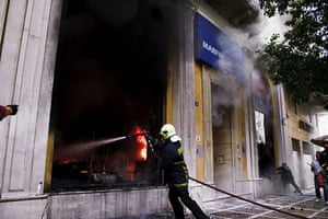 Greece Riots: A firefighter tries to extinguish a fire at the Marfin Egnatia Bank