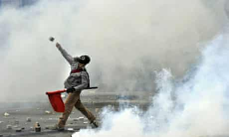 A protester throws a stone at police near parliament.