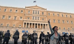 A woman shouts anti-government slogans in front of  riot police outside parliament in Athens