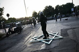 Israel protests: A policeman stands in a handmade Star of David in Athens
