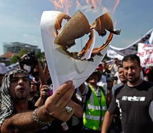 Israel protests: Protesters burn a photograph of Netanyahu in Kuala Lumpur