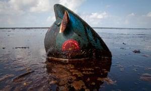 An oil worker's hard hat lies in oil from the Deepwater Horizon spill.