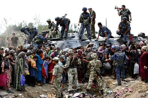 Uzbek refugees: Refugees line up around an armoured vehicle in the Kyrgyz city of Osh