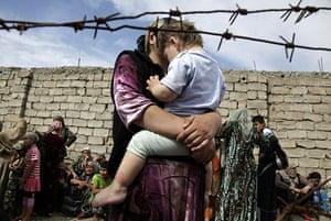 Uzbek refugees: A mother holds her son as they wait at the Kyrgyz-Uzbek border