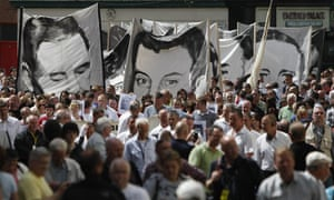 Banners bearing portraits of Bloody Sunday victims are carried to the Guildhall.