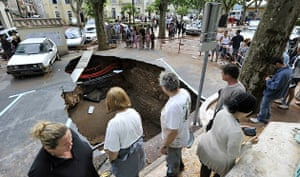 Flooding in France: Les Arcs sur Argens: People look at a hole in a car park caused by flooding