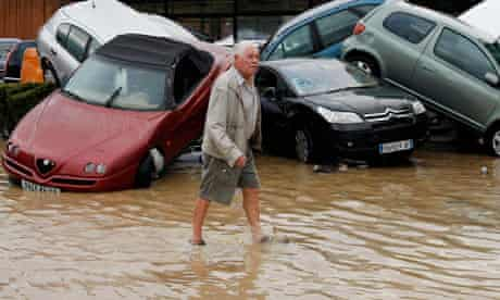 A man walks past damaged cars in Draguignan after heavy flooding in France